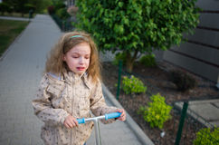 The little girl goes on the sidewalk and cries. Royalty Free Stock Images