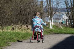 Little girl is going away on a retro tricycle Stock Photo