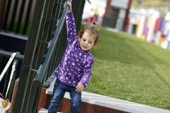 Little girl going down some stairs outdoors. Little 20-month-old girl going down some stairs outdoors royalty free stock image