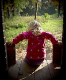 Little girl going out from a wooden house. A little caucasian happy blond girl child getting out of a wooden house in the garden outdoors. She wears pink jacket stock photography