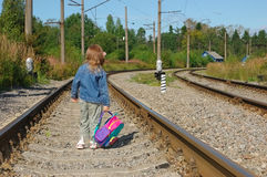 The little girl going on railway. The little girl going with a backpack on railway rails royalty free stock photo