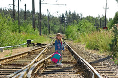 The little girl going on railway. The little girl going with a backpack on railway rails Stock Photos