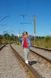 The little girl going on railway rails. The little girl going with a backpack on railway rails Royalty Free Stock Photos