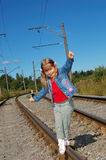 The little girl going on railway rails. The little girl going with a backpack on railway rails Royalty Free Stock Photography