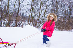 Little girl going sledding in snowy winter day Royalty Free Stock Image