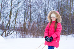 Little girl going sledding in snowy winter day Royalty Free Stock Images