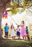 Little girl is going to broke the pinata for her birthday. In a park Stock Images