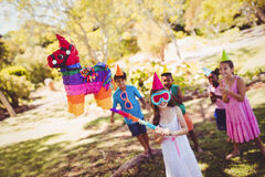 Little girl is going to broke the pinata for their birthday. In a park Royalty Free Stock Image