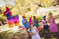 Little girl is going to broke the pinata for their birthday royalty free stock image