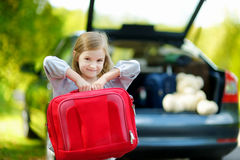 Little girl going to a car vacation. Adorable little girl with a suitcase leaving for a car vacation with their parents Royalty Free Stock Photos