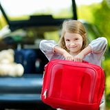 Little girl going to a car vacation. Adorable little girl with a suitcase leaving for a car vacation with their parents Royalty Free Stock Image