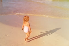 Little girl going to swim at beach Stock Images