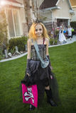 Little girl going trick or treating on Halloween in her costume. Cute little girl dressed in Halloween zombie witch costume going trick or treating outdoors in Royalty Free Stock Image