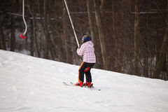 Little girl going up by ski lift Stock Photography