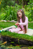 Little girl with gold fishes near pond Royalty Free Stock Image