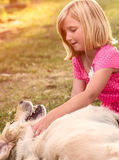 Little girl with golden retriever dog. Young girl hugging golden retriever dog in the park Royalty Free Stock Image