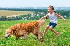 Little girl with golden retriever Stock Images