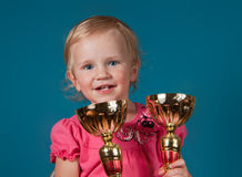 Little girl with golden trophies Royalty Free Stock Photography