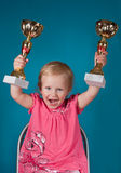 Little girl with golden trophies Stock Photos