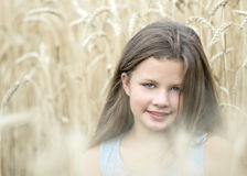 Little girl in golden wheat field in summer day. Portrait of a beautiful child. Concept of purity, growth, happiness royalty free stock images