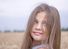 Little girl in golden wheat field in summer day. Portrait of a beautiful child. Concept of purity, growth, happiness stock image