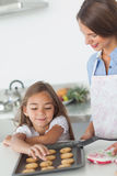 Little girl grabbing a cookie from a baking pan Royalty Free Stock Photos