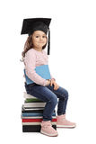 Little girl with graduation hat sitting on pile of books Stock Image