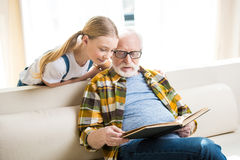 Little girl with grandfather in eyeglasses reading book together Royalty Free Stock Photo