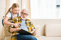 Little girl with grandfather in eyeglasses reading book together Stock Photos