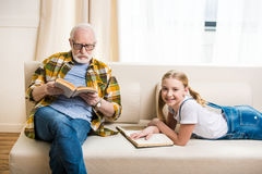 Little girl with grandfather in eyeglasses reading books on sofa Stock Photos
