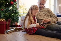 Little girl with grandfather sitting by christmas tree and using royalty free stock photo