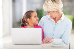 Little girl grandma laptop. Cheerful little girl and grandma using laptop computer at home Royalty Free Stock Photo
