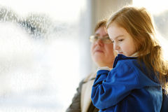 Little girl and grandma staring through a window Royalty Free Stock Photo