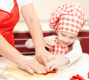 Little girl and grandmother cut dough with form  for cookies Stock Photo