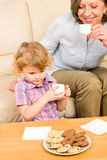 Little girl with grandmother eat cookies Stock Image