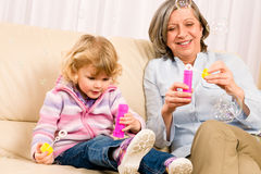 Little girl with grandmother play bubble blower Stock Photography