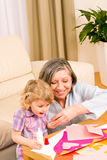 Little girl with grandmother play glue paper Royalty Free Stock Images