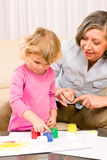 Little girl with grandmother play paint handprints. Granddaughter with grandmother play making handprints painting at home royalty free stock photography