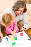 Little girl with grandmother play paint handprints Stock Photography