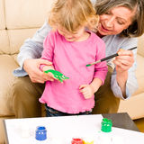 Little girl with grandmother play paint handprints. Grandmother with granddaughter playing together paint handprints on paper stock photography