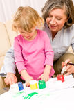 Little girl with grandmother play paint handprints stock image