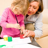Little girl with grandmother play paint handprints Royalty Free Stock Photography