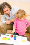 Little girl with grandmother play paint handprints Royalty Free Stock Photo