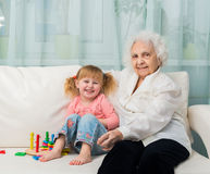 Little girl with grandmother on a sofa Royalty Free Stock Images