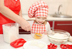 Little girl and grandmother stirrring cookie doug Stock Photography