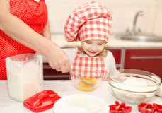 Little girl and grandmother stirrring cookie doug Royalty Free Stock Photos