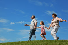 Little girl and grandparents running on hill Stock Photo