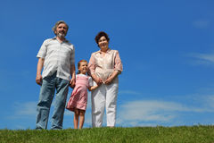 Little girl and grandparents standing on lawn Royalty Free Stock Photography