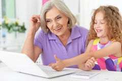 Little girl   with granny using laptop Royalty Free Stock Images