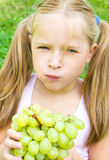 Little girl with grapes. Little girl is eating grapes outdoors Royalty Free Stock Photography